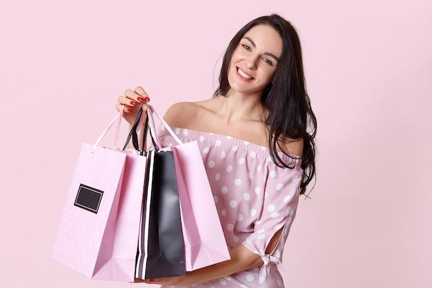 Mensen en winkelen concept. gelukkig donkerharige vrouw shopaholic gekleed in polka dot jurk, draagt boodschappentassen, geïsoleerd op roze, heeft rode manicure. vrouwelijke klant staat binnen Gratis Foto