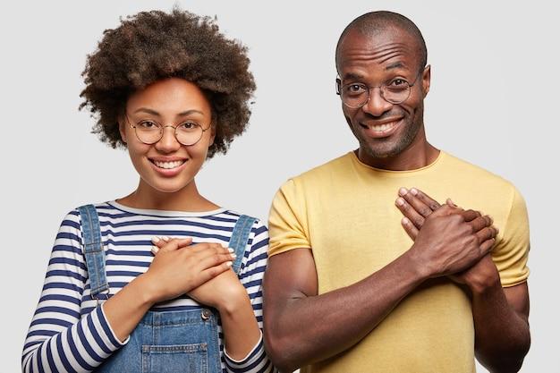 Mensen, etniciteit en dankbaarheid concept. glimlachende jonge vrouw en man houden handen op de borst Gratis Foto