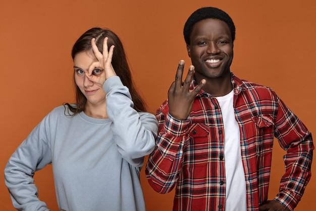 Mensen, etniciteit, vriendschap en liefde. emotionele grappige jonge zwarte man gebaren en glimlachen, staande naast zijn witte vriendin die door cirkel tussen vingers Gratis Foto