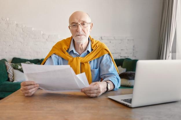 Mensen, financiën, technologie en baanconcept. ernstige modieuze gepensioneerde zakenman financiën op moderne kantoor te doen, papieren in zijn handen te houden, open laptop op houten tafel in van hem Gratis Foto