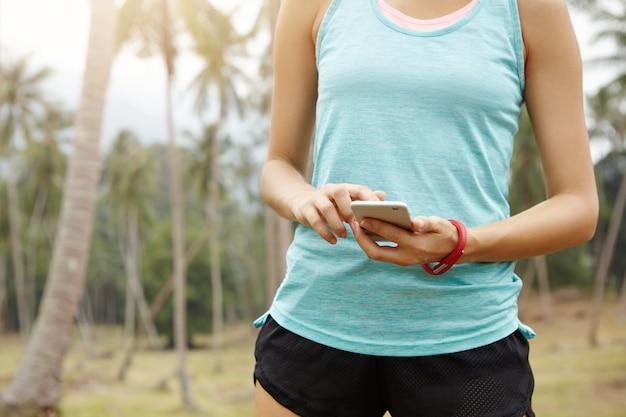Mensen, fitness en technologieconcept. buik van vrouwelijke atleet in sportkleding met behulp van mobiele telefoon, instellingen op app controleren voor het volgen van haar voortgang. Gratis Foto