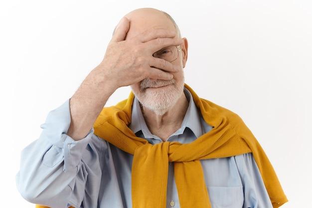 Mensen, gebaren en tekens concept. stijlvolle blanke oudere ongeschoren man draagt een bril en elegante kleding houdt de palm op zijn gezicht en gluurt naar de camera met zijn vingers, geïsoleerd poseren Gratis Foto