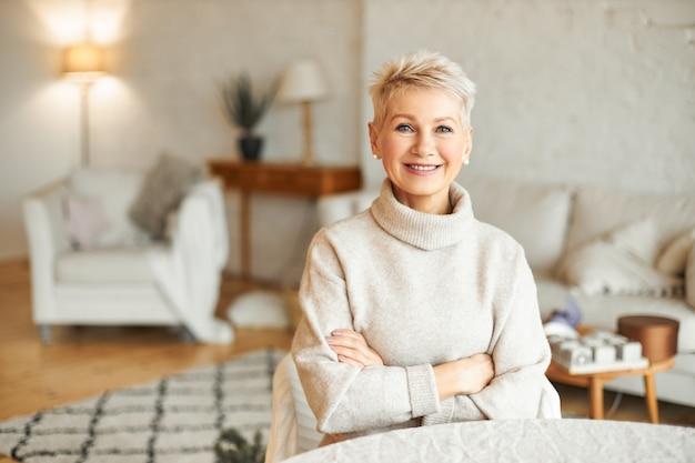 Mensen, gezelligheid, huiselijkheid en seizoenconcept. charmante mooie gepensioneerde vrouw vrije tijd binnenshuis thuis doorbrengen met zelfverzekerde glimlach, armen gevouwen op haar borst Gratis Foto