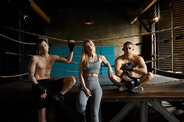 Mensen, gezondheid, activiteit en lichamelijke oefeningen. drie fitte kaukasische atleten poseren binnenshuis: stijlvolle blonde meisje in grijze outfit zittend op boksring tussen twee mannen met gespierde naakte torso Gratis Foto