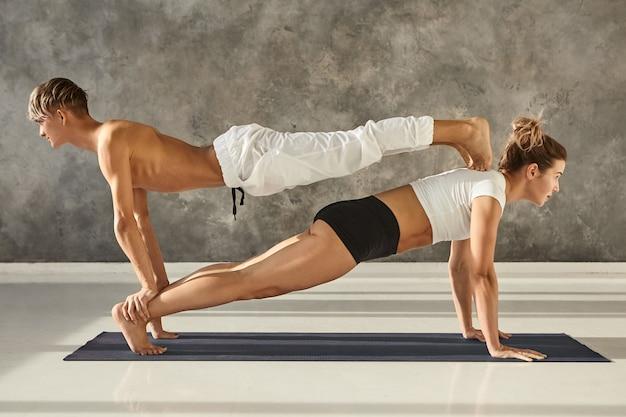 Mensen, gezondheid, sport, activiteit, fitness, pilates en acrobatiekconcept. jonge atletische paar mannelijke en vrouwelijke partner yoga samen beoefenen op sportschool, dubbele plank op een mat doen, man bovenop Gratis Foto