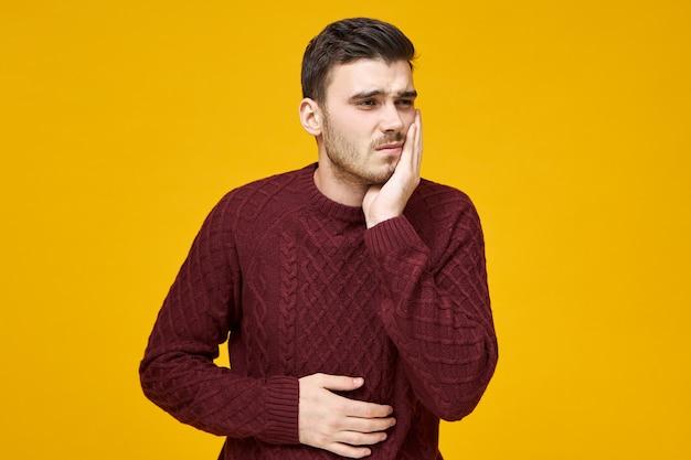 Mensen, gezondheidszorg, tandheelkunde en ziekteconcept. depressieve, verstoorde jonge ongeschoren man met pijnlijke gestreste gezichtsuitdrukking die lijdt aan kiespijn, zich ziek voelt, hand op wang en buik houdt Gratis Foto