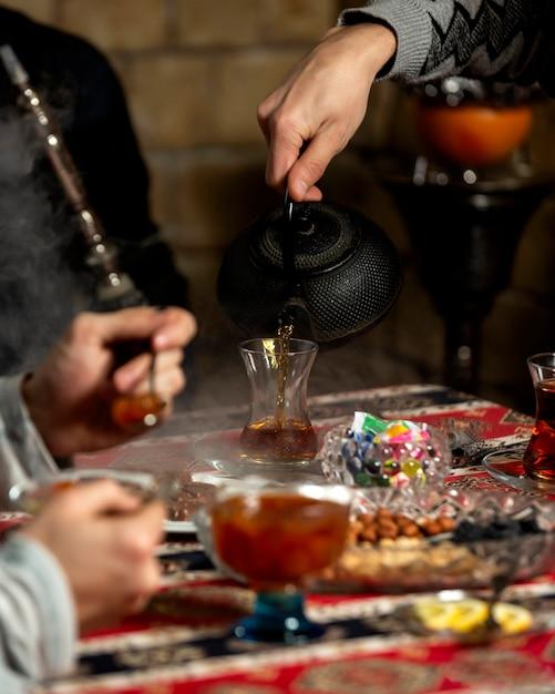 Mensen gietende thee in armudu-glas in azerbeidzjaanse traditionele theeopstelling Gratis Foto