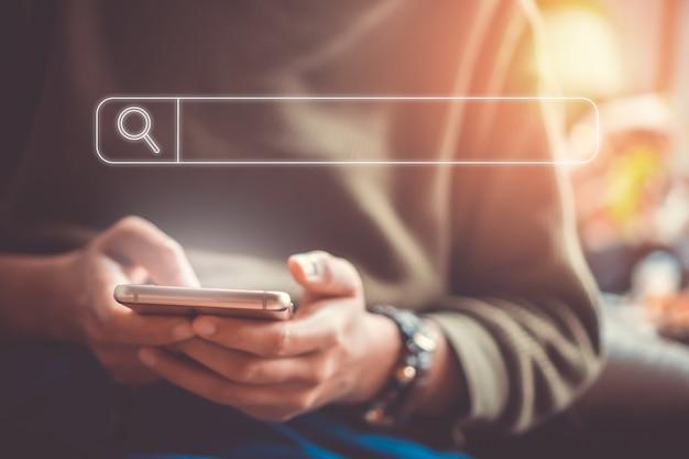 Mensen hand met behulp van mobiele telefoon of smartphone op zoek naar informatie in internet online samenleving web met zoekvak pictogram. Premium Foto