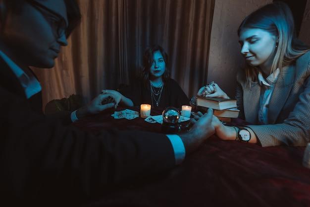 Mensen houden de hand van de nacht aan tafel vast met kaarsen Gratis Foto