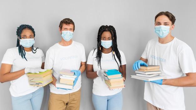 Mensen houden een hoop boeken vast om ze te doneren Gratis Foto