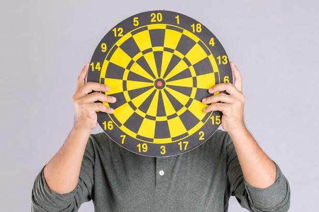 Mensen houden geel dartbord vast en verbergen zijn gezicht. Premium Foto