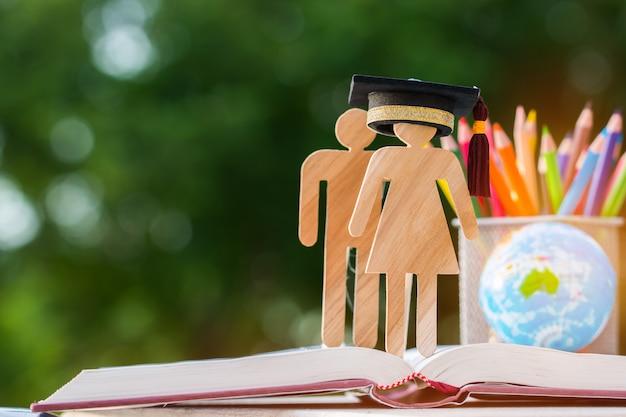 Mensen houten bord met afstuderen dop op open leerboek Premium Foto