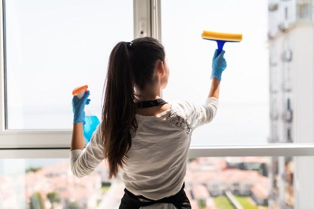 Mensen, huishoudelijk werk en huishouden concept. gelukkige vrouw die in handschoenen venster met vod en reinigingsnevel thuis schoonmaken Gratis Foto
