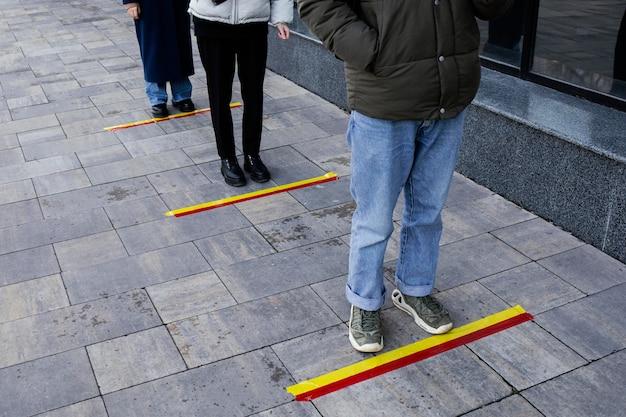 Mensen in de rij wachten achter sociale afstandsstreep Gratis Foto