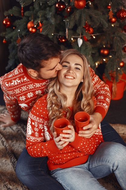 Mensen in een kerstversiering. man en vrouw in een rode trui. Gratis Foto