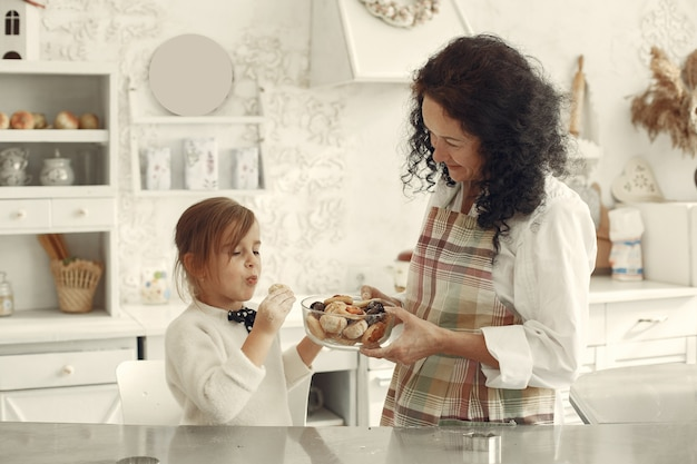 Mensen in een keuken. grootmoeder met dochtertje. de volwassen vrouw geeft meisjekoekjes. Gratis Foto