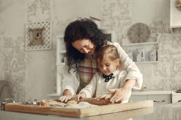 Mensen in een keuken. grootmoeder met dochtertje. volwassen vrouw leert meisje koken. Gratis Foto