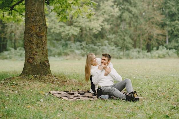 Mensen in een park. vrouw in een bruine jas. man in een witte trui. koppel in een picknick. Gratis Foto