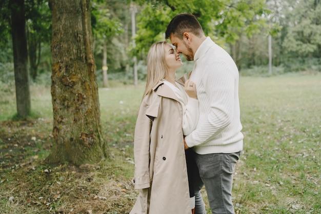 Mensen in een park. vrouw in een bruine jas. man in een witte trui. Gratis Foto