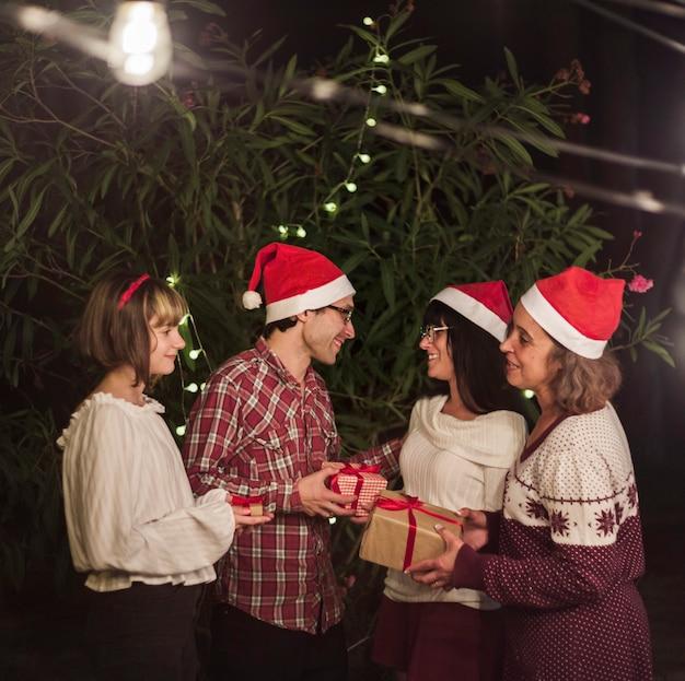 Mensen in kerstmutsen die geschenken uitwisselen Gratis Foto