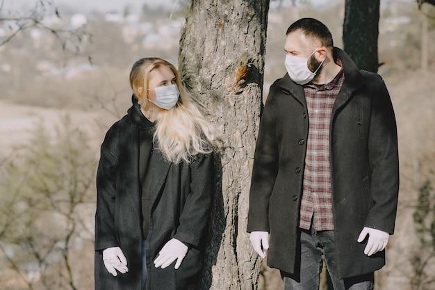 Mensen in maskers wandelingen in een bos Gratis Foto