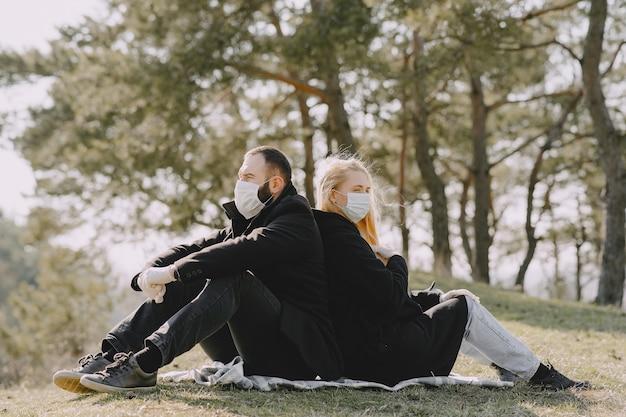Mensen in maskers zitten in een bos Gratis Foto