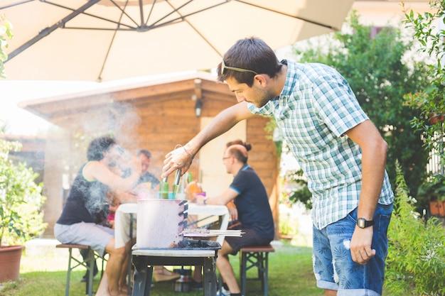 Mensen kokend vlees op de barbecue Premium Foto