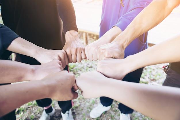 Mensen komen samen hand in hand tijdens hun werk - concept van menselijke betrokkenheid Gratis Foto