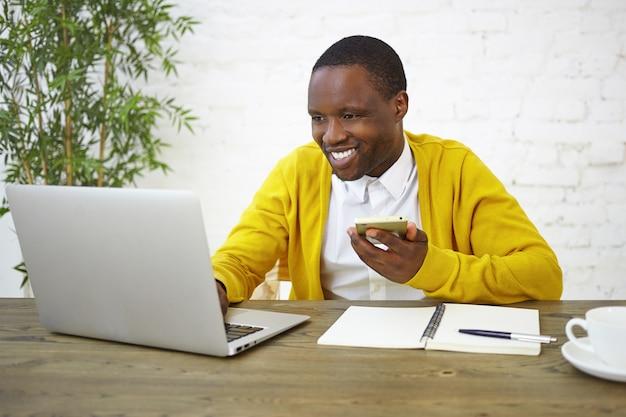 Mensen, levensstijl, baan, technologie en communicatieconcept. vrolijke afro-amerikaanse mannelijke freelancer in helder geel vest met behulp van mobiele telefoon en draagbare computer in kantoor aan huis, breed glimlachend Gratis Foto