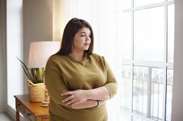 Mensen, levensstijl en lichaamspositiviteitsconcept. mooie jonge brunette vrouw met extra kilo staan bij raam thuis, armen gekruist op haar borst, doordachte peinzende blik, peinzend Gratis Foto