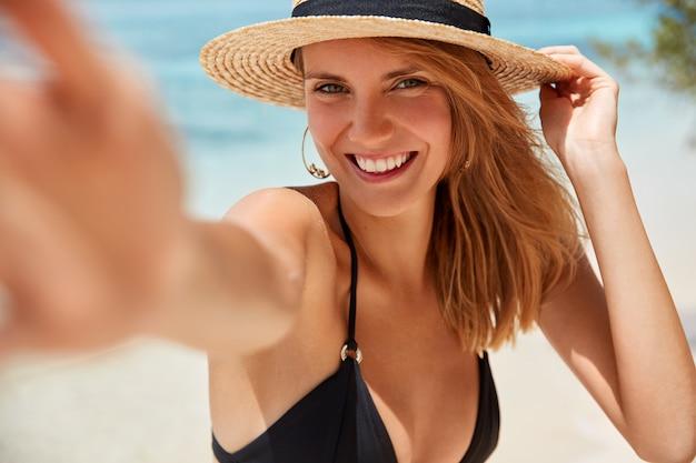 Mensen, levensstijl, geluk en zomertijd concept. mooie jonge lachende vrouw met vrolijke uitdrukking vormt voor het maken van selfie tegen azuurblauwe zee achtergrond, blij om een goede onvergetelijke rust te hebben Gratis Foto