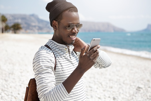 Mensen, levensstijl, reizen, avontuur en moderne technologie concept. knappe vrolijke afro-amerikaanse backpacker in hoed en zonnebril met mobiele telefoon Gratis Foto