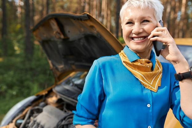 Mensen, levensstijl, transport en modern technologieconcept. mooie blonde gepensioneerde vrouw stond door kapotte auto met open kap, pechverhelping bellen, om hulp te vragen, glimlachend Gratis Foto