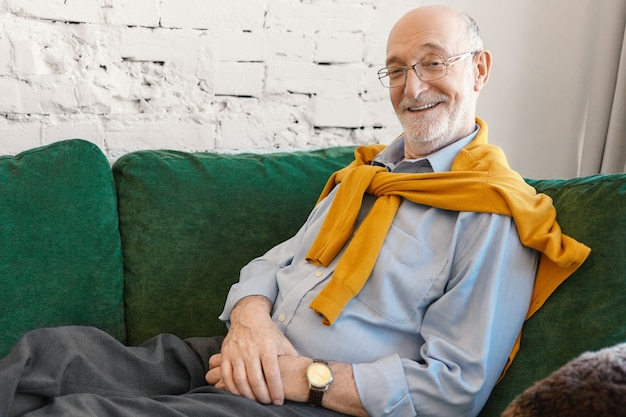 Mensen, levensstijl, vreugde, rust en ontspanningconcept. horizontaal schot van knappe emotionele 70-jarige grootvader die elegante kleding en bril draagt die thuis op de bank ontspant, breed glimlachend Gratis Foto