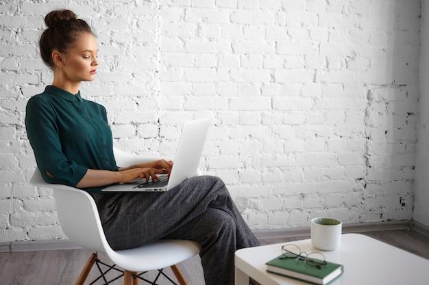 Mensen, levensstijl, vrije tijd, technologie en communicatieconcept. modieuze jonge vrouwelijke blogger werkt op afstand met behulp van wifi op de draagbare computer op haar schoot, snel typen, met koffie in de ochtend Gratis Foto