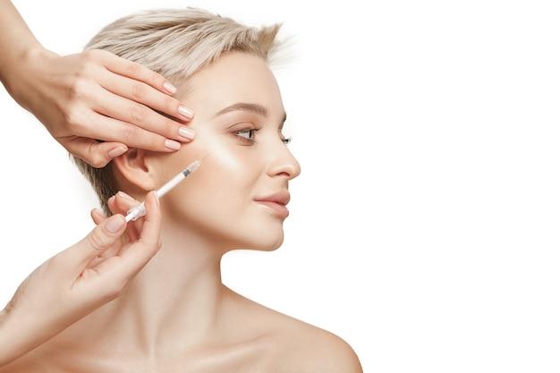 Mensen, lippen, cosmetologie, plastische chirurgie en schoonheid concept - mooie jonge vrouw gezicht en hand met spuit injectie maken Gratis Foto