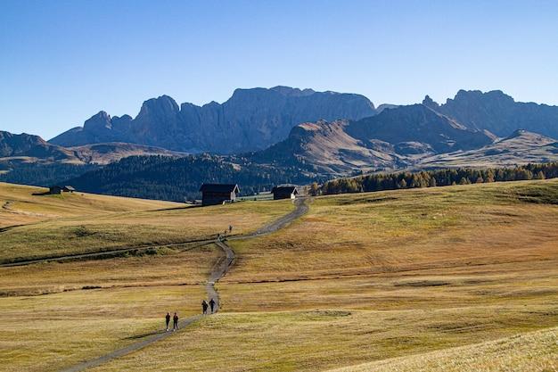 Mensen lopen op een pad midden tussen grasvelden met gebouwen in de verte Gratis Foto