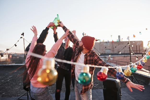 Mensen maken een toast. vakantie op het dak. vrolijke groep vrienden staken hun handen omhoog met alcohol Gratis Foto