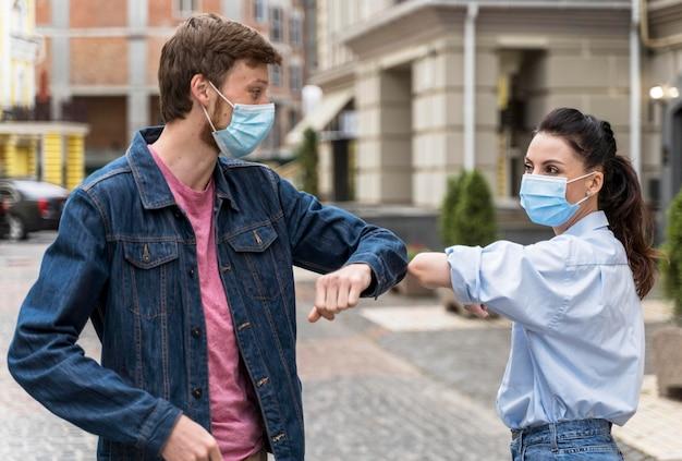 Mensen met gezichtsmaskers stoten elleboog Premium Foto