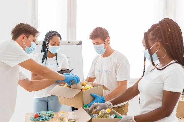 Mensen met medische maskers die pakketten met donaties voorbereiden Premium Foto