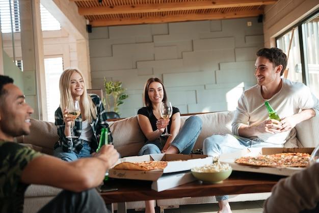 Mensen met pizza, wijn en bier zitten en praten Premium Foto