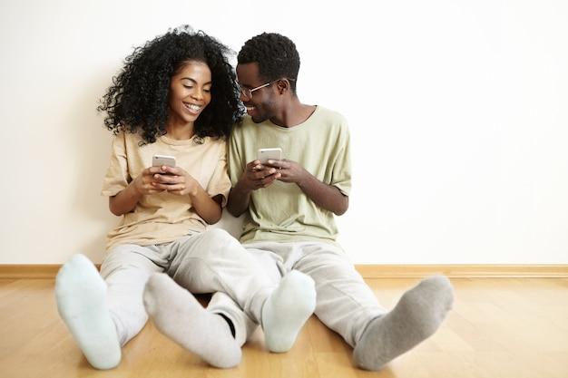 Mensen, moderne technologie en vrijetijdsconcept. gelukkig jong donker-huidig paar die gelijkaardige kleren dragen die op vloer in slaapkamer ontspannen en elektronische gadgets gebruiken Gratis Foto
