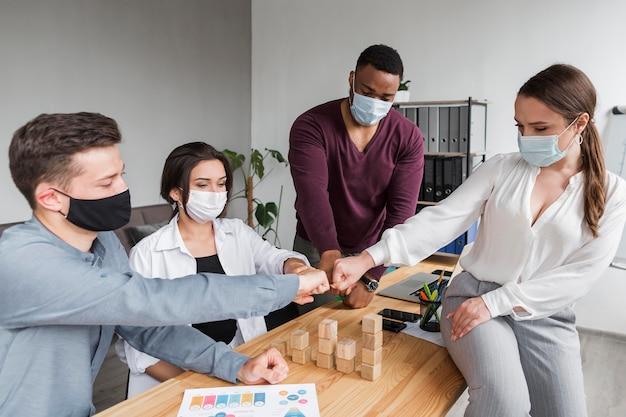 Mensen op kantoor tijdens een pandemie die een vergadering hebben en elkaar stoten Gratis Foto