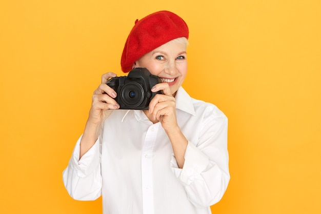 Mensen, ouder worden, pensioen en creatief beroepsconcept. portret van senior vrouwelijke fotograaf in witte blouse en rode motorkap full frame dslr camera te houden Gratis Foto