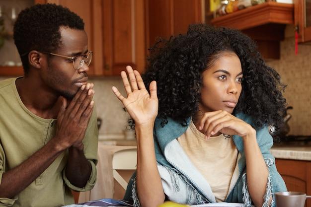 Mensen, relatieproblemen en echtscheiding. berouwvol bezorgd man met donkere huidskleur die de handen in elkaar gedrukt houdt, smekend beledigde vrouw om zijn ontrouw te vergeven, gekke vrouw die helemaal niet naar hem kijkt Gratis Foto