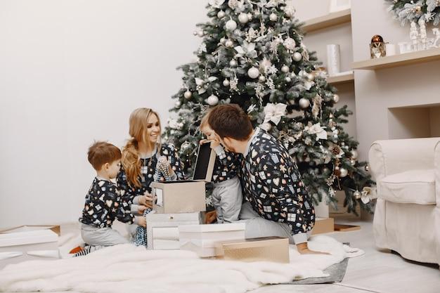 Mensen repareren voor kerstmis. mensen spelen met kind. familie rust in een feestelijke kamer. Gratis Foto
