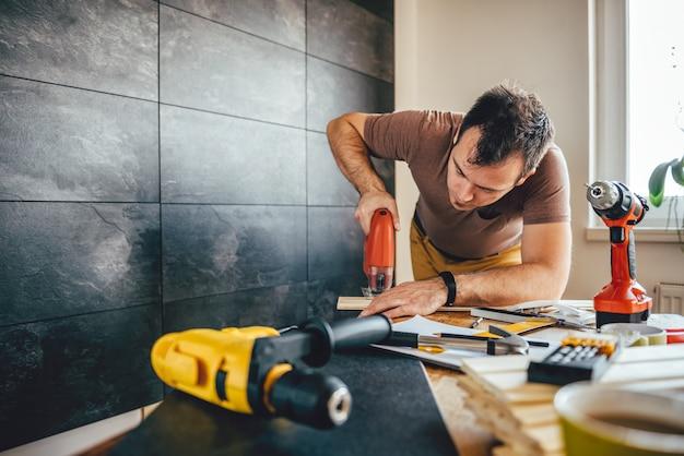 Mensen scherp hout met elektrische figuurzaag Premium Foto