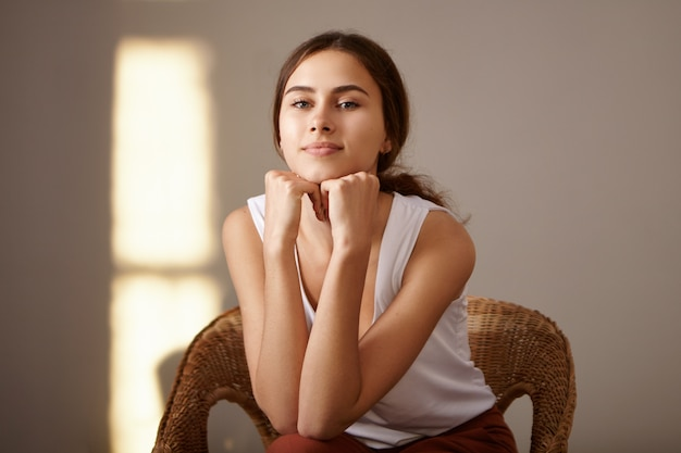 Mensen, schoonheid en jeugdconcept. indoor portret van charmante gebruinde slanke jonge europese vrouw ontspannen thuis zitten in geweven fauteuil alleen, handen onder haar kin. gouden uurzon Gratis Foto