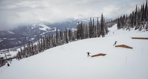 Mensen skiën op besneeuwde alpen in skigebied Gratis Foto