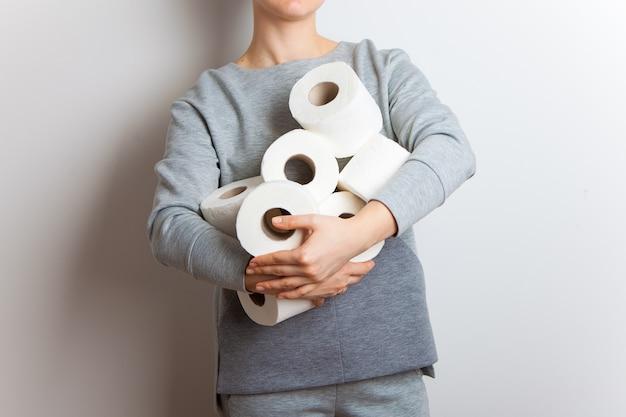 Mensen slaan wc-papier op. vrouw houdt vele rollen wc-papier Premium Foto
